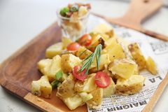 Potato salad on wooden plate. In close up stock photos