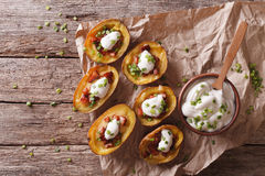 Potato skins with cheese, bacon and sour cream on the table. Hor Royalty Free Stock Photos