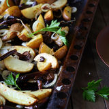 Potato slices with mushrooms and onions on a baking sheet Stock Photo