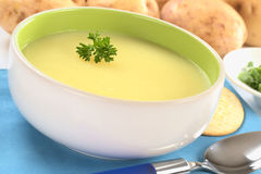 Potato Soup. Fresh potato cream soup garnished with a parsley leaf with green onion and raw potatoes in the back on a blue table mat (Selective Focus, Focus on stock images