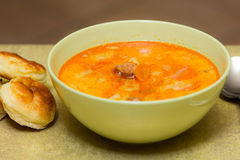 Potato soup with sausages. In green bowl and scones Stock Images