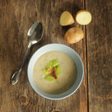 Potato soup. Top view of a potato soup in a blue bowl with fresh potatoes and spoon on a wooden background stock photo