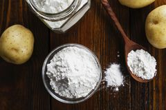 Potato starch in a glass bowl. On wooden table stock photos