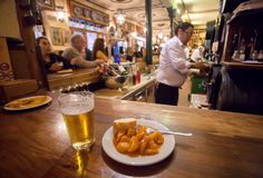 Potato tapas on plate and glass of beer for customer of busy fast-food restaurant in traditional spanish style stock photo