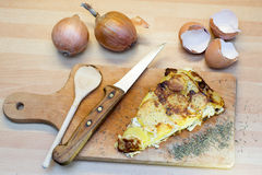 Potato tortilla. Slice of potato tortilla on wooden cutting board with egg shells, herbs and yellow onions royalty free stock image