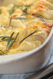 Potato and turnip gratin. With rosemary in the white casserole stock photography