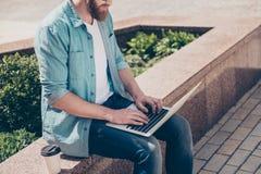 Potato vicino sulla foto del tipo barbuto che lavora al computer portatile fuori, Immagini Stock