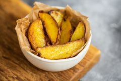 Fried organic potato slices on parchment in bowl on wooden board. Copy space. Close up royalty free stock photos