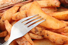 Potato wedges and fork Stock Photos