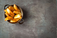 Potato wedges fries. Bowl of chunky potato wedges fries served on a rustic stone, slate, gray table top Stock Image