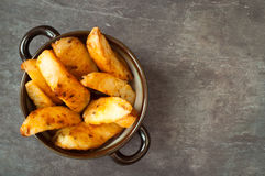Potato wedges fries. Bowl of chunky potato wedges fries served on a rustic stone, slate, gray table top Stock Photography