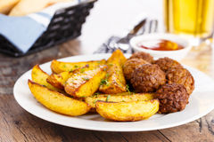 Potato wedges and meatballs Stock Photography
