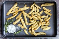 Potato Wedges with Rosemary and Sea Salt Top View on Oven Tray. Potato wedges on baking tray, top view, with rosemary and sea salt stock image