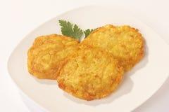 Potatoe Loafs - Kartoffelpuffer. Potatoe loafs on a white plate on white background - Kartoffelpuffer auf Teller vor weissem Hintergrund stock image
