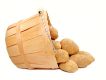 Potatoes. A group of potatoes flowing from a wooden harvest basket, on white Royalty Free Stock Photography
