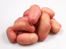 Potatoes. Pink potatoes arranged on white background Stock Images