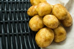 Potatoes against a black basket and napkin. royalty free stock photography