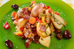 Potatoes baked with bacon served on plate. Homemade food preparation. Stock Photos