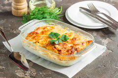 Potatoes baked with cheese, apples and vegetables. Potato gratin with cream cheese and fresh herbs Stock Photo