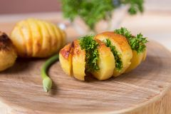 Potatoes baked with fresh herbs, lined on a wooden stand. stock images
