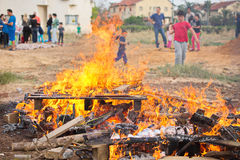 Potatoes baking in a bonfire. TEL AVIV, ISRAEL - MAY 3, 2015: Baked potatoes covered with aluminum foil roasting in a Lag Baomer bonfire with orange flames and Royalty Free Stock Image