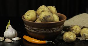 Dirty raw potatoes on a plate on table with garlic and pepper stock photos