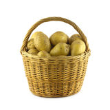 Potatoes in brown wicker basket isolated closeup. Many ripe potatoes in brown wicker basket isolated on white closeup Stock Images