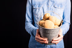 Potatoes bucket in hands Royalty Free Stock Photography