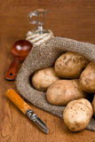 Potatoes in burlap sack with a rustic knife Stock Photos