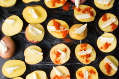 Potatoes with butter and ground red pepper. On black plate stock images