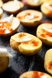 Potatoes with butter and ground red pepper. On black plate royalty free stock photography
