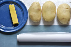 Potatoes, butter and parchment paper. Three potatoes, a stick of butter and a roll of parchement paper Stock Photo
