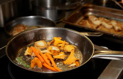 Potatoes, carrots and mushrooms being fried in pan Stock Photos