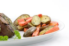 Potatoes and carrots, roasted. Serving platter for two with rack of lamb, roasted fingerling potatoes and carrots garnished with thyme and parsley royalty free stock photo