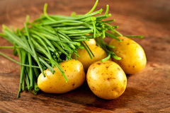 Potatoes and chives. Fresh potatoes and chives on wood Royalty Free Stock Photo