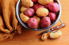 Potatoes in Colander with Burlap Sack Stock Images
