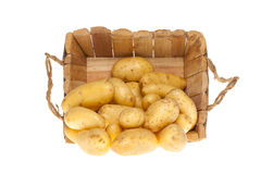 Potatoes coming out a wooden basket Stock Photography