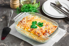 Potatoes cooked in the oven, baked with apples and cheese. Potato gratin with cream cheese and fresh herbs Royalty Free Stock Images