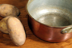 Potatoes and Copper Cooking Pot. This is an image of potatoes and a copper cookpot on a wooden countertop stock image