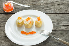 Potatoes, with creme fraiche and salmon caviar Royalty Free Stock Photo