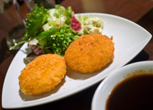 Potatoes Croquette. Mashed potatoes breadcrumbed fried served with fresh salad Stock Photo
