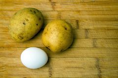Potatoes and Egg on wooden table - Ingredients - top focus. Fresh ingredients on a wooden table with copy space to the right. Top view with narrow focus Royalty Free Stock Images