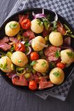 Potatoes with fried bacon and herbs on a plate, top view Royalty Free Stock Image