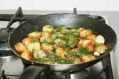 Potatoes fried on the stove. Delicious vegetables fried home made on a pan Stock Photo