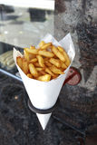 Potatoes fries in a little white paper bag Stock Photography