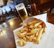 Potatoes fries. In a little white paper bag on wood table in brussels pub Royalty Free Stock Images
