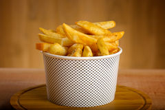 Potatoes fries in a white paper bag on wooden Stock Photo