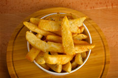 Potatoes fries in a white paper bag on wooden Royalty Free Stock Photo