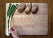 Potatoes and green onions on chopping block Royalty Free Stock Images