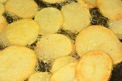 Potatoes on the iron frying pan Stock Photos